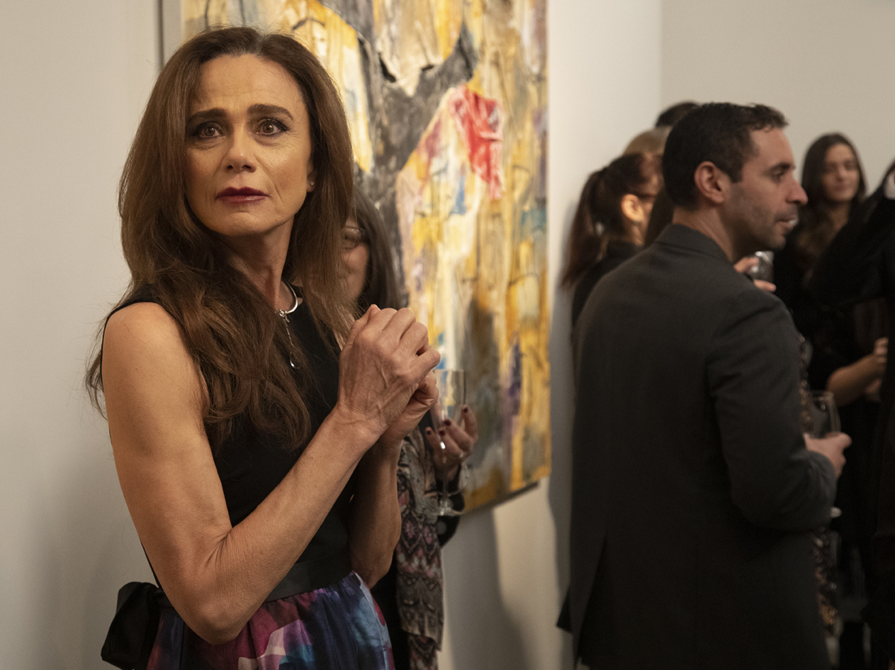 Claire (Lena Olin) hesitantly takes in the scene at Richard's long-awaited opening in THE ARTIST'S WIFE. Photo by Michael Lavine.
