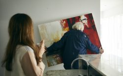 Richard (Bruce Dern) unexpectedly removes a painting from the wall as Claire (Lena Olin) looks on in THE ARTIST'S WIFE. Photo by Michael Lavine.